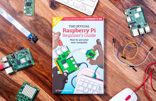Raspberry Pi Beginner's Guide book on a table surrounded by Raspberry Pi products